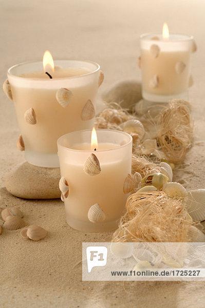 Kerzen mit Muscheldeko im Sand
