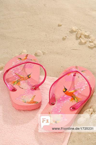 Pink flip flops in the sand