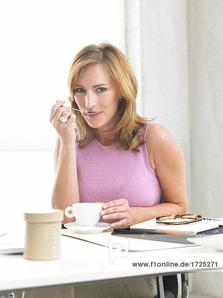 Frau sitz am Schreibtisch und trinkt Kaffee