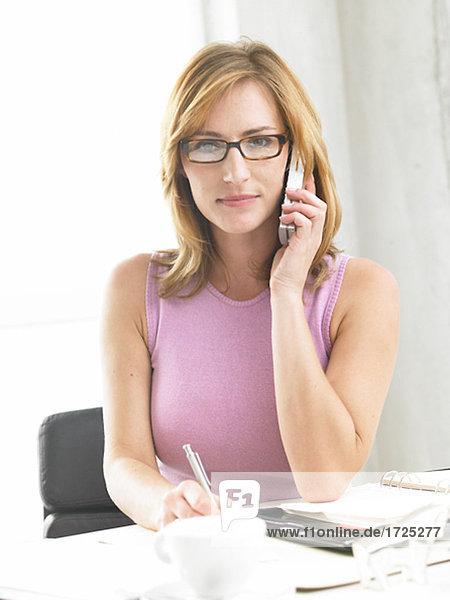 Geschäftsfrau schreibt und telefoniert