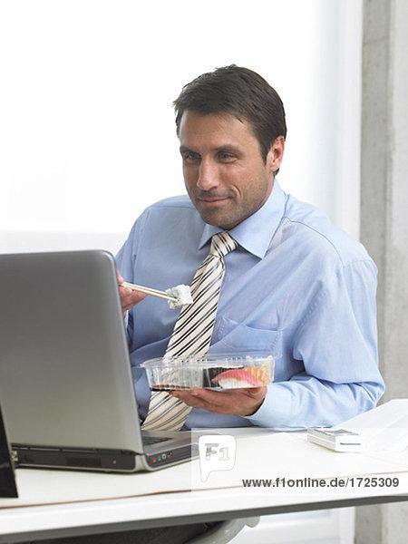Mann isst Sushi am Arbeitsplatz