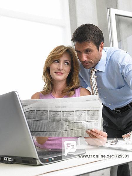 Geschäftsmann- und Frau lesen die Zeitung