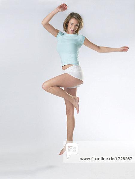Frau mit T-Shirt und Shorts hebt das Bein