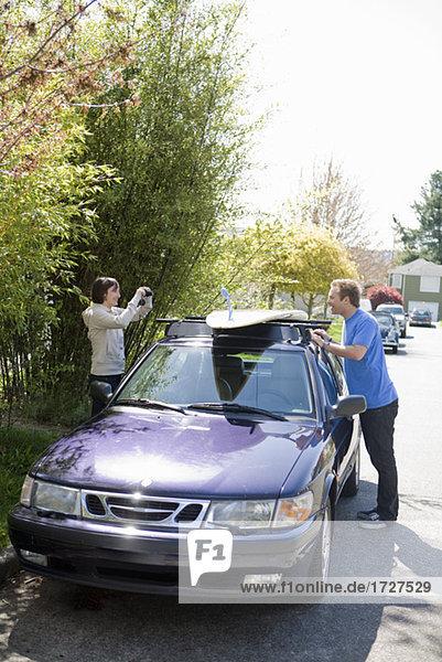 Frau fotografieren Mann mit dem Auto