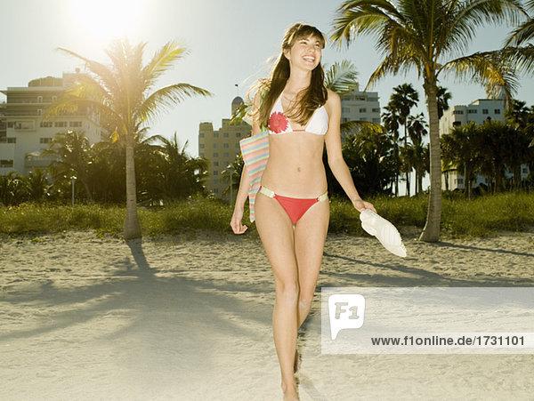 Teenage girl in bikini walking on beach