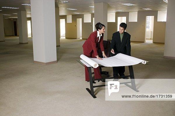 Firmen betrachten Blueprints in leeren office