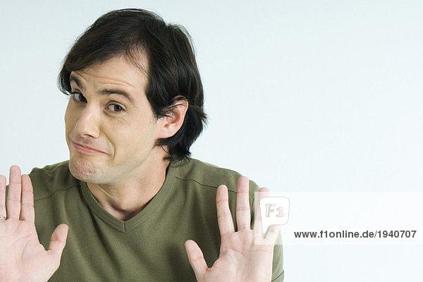 Mann  Augenbrauen heben  Handflächen hochhalten  Portrait