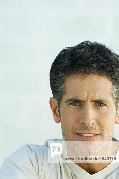 Mann mit zusammendrückenden Zähnen und furchender Stirn  Portrait