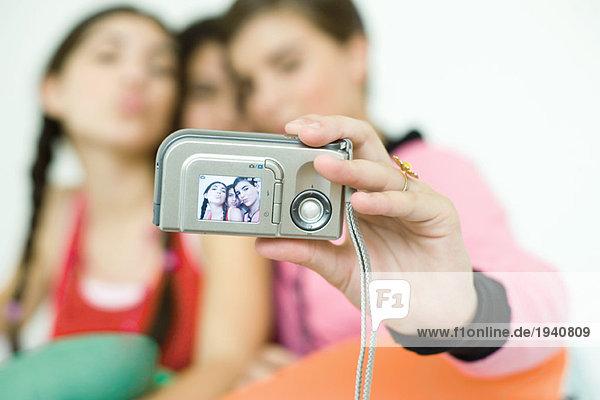 Drei junge Freundinnen fotografieren sich selbst mit Digitalkamera  Fokus auf Kamera im Vordergrund