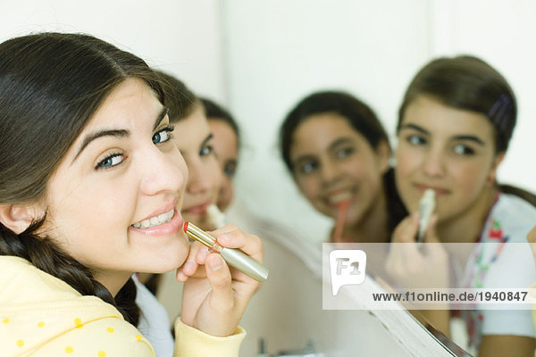 Young female friends putting on make-up mouth