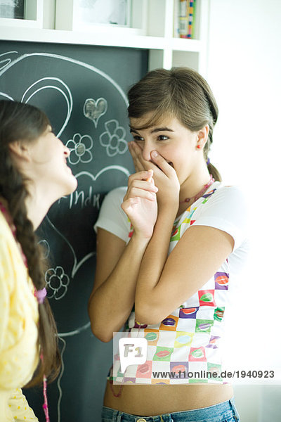 Young female friends writing names in hearts on chalkboard  laughing