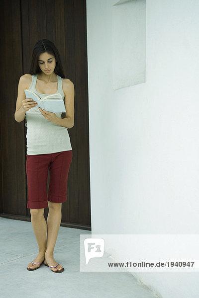 Woman standing reading book  full length portrait