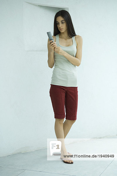 Woman standing dialing cell phone  full length portrait