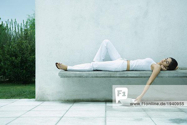 Frau liegt auf dem Rücken und lässt das Buch zu Boden fallen.