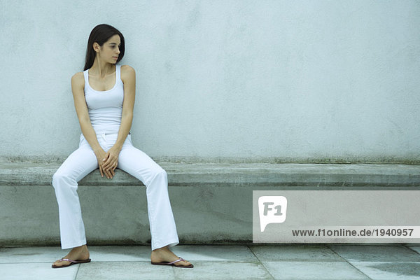 Woman sitting on bench  looking at empty place next to her