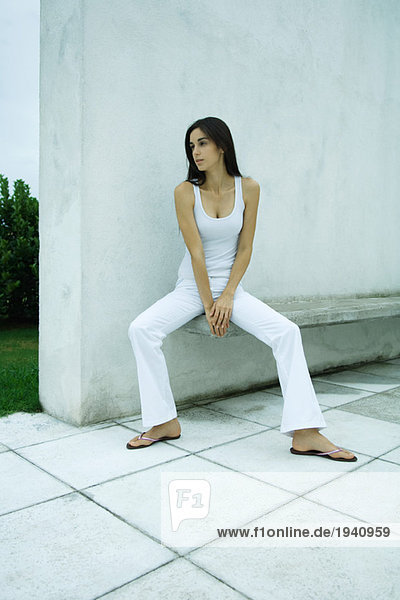 Woman sitting on bench  looking away  full length
