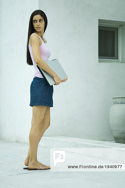 Woman standing  holding laptop computer  looking over shoulder  full length portrait