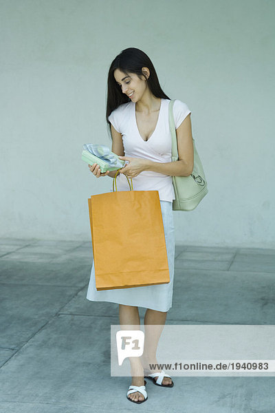 Woman holding shopping bag and gift  full length portrait