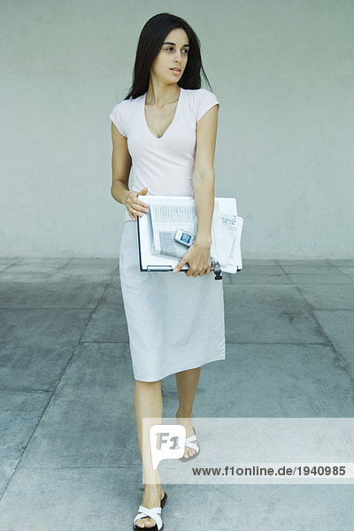 Woman carrying laptop  newspaper and cell phone under arm  full length portrait