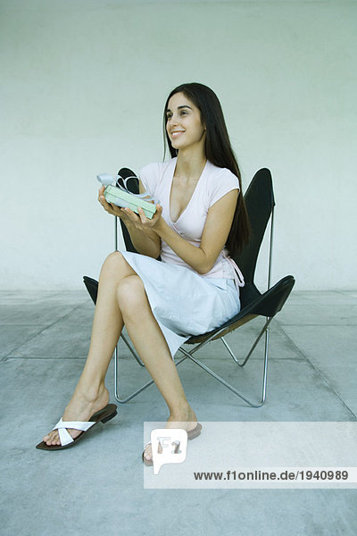 Young woman sitting in chair  holding up gift  full length portrait