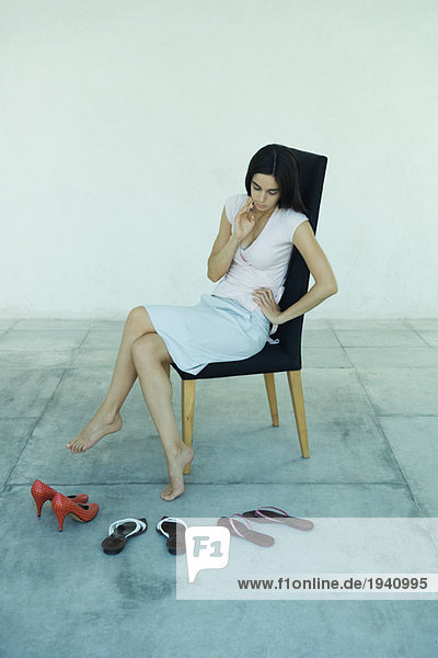 Young woman sitting in chair  looking down at three pairs of shoes  full length portrait