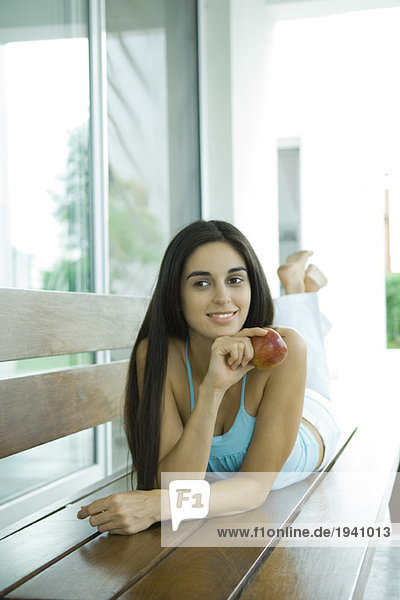 Young woman lying on bench  holding apple  full length