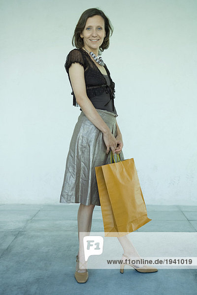 Mature woman standing with shopping bag  full length portrait