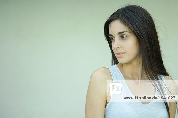 Young woman  looking away  head and shoulders  portrait