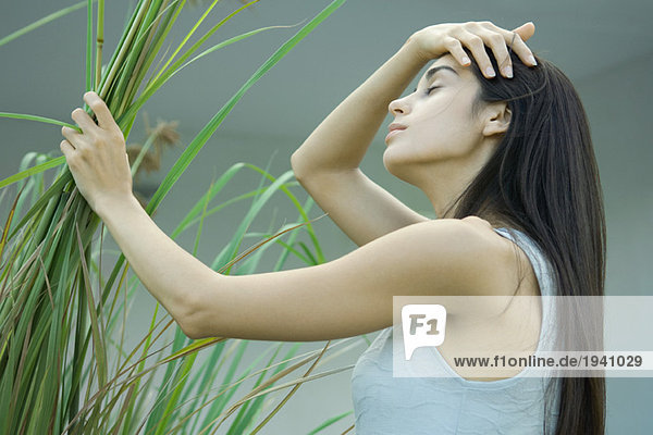Young woman holding handful of plant stems  pushing hair back  eyes closed