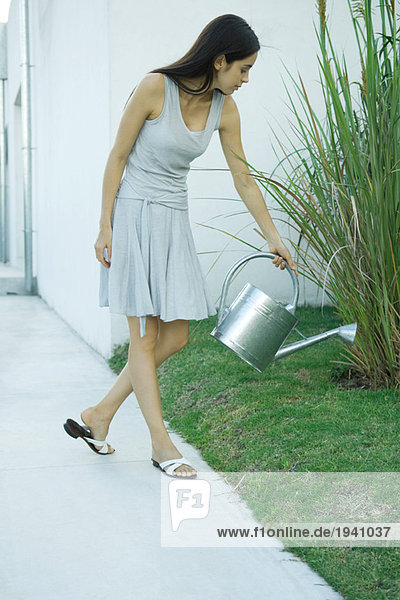 Woman watering garden with watering can  full length portrait