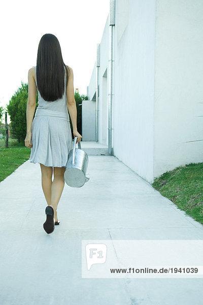Frau mit Gießkanne  Rückansicht  volle Länge