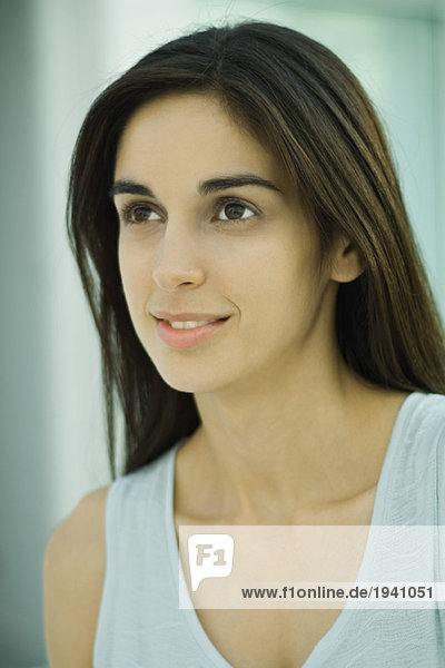 Young woman  looking up  head and shoulders  portrait