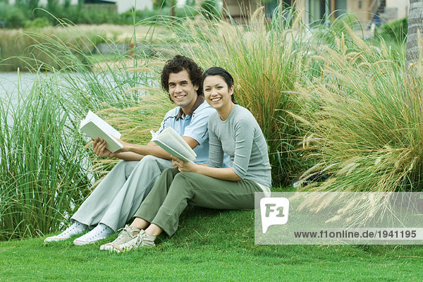 Paar auf Gras sitzend mit Büchern  lächelnd vor der Kamera