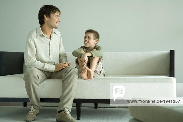 Junge und Vater sitzen auf dem Sofa und reden.