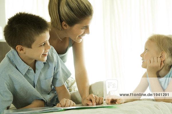 Mutter hilft Kindern bei den Hausaufgaben