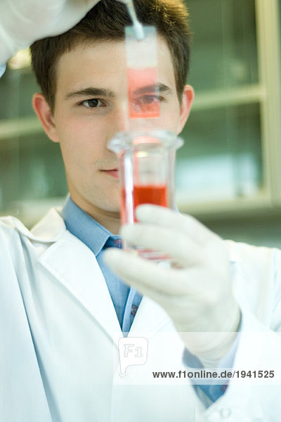 Young male scientist dipping microscope slide into solution in test tube  holding up slide
