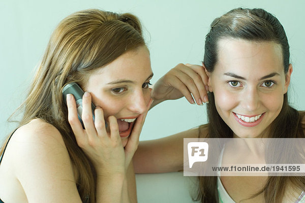 Two young friends smiling together  using cell phone  one looking at camera