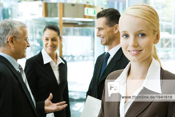 Junge Geschäftsfrau lächelt vor der Kamera  Mitarbeiter plaudern im Hintergrund