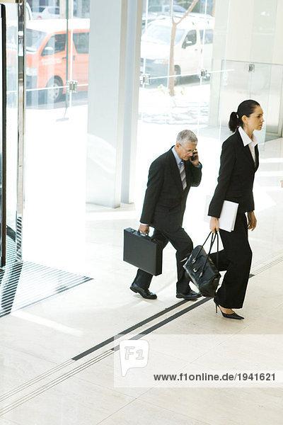 Geschäftsfreunde  die in der Lobby spazieren gehen  einer mit dem Handy  volle Länge