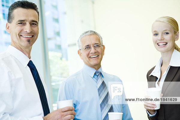 Drei Geschäftspartner lächelnd vor der Kamera  mit heißen Getränken  Portrait