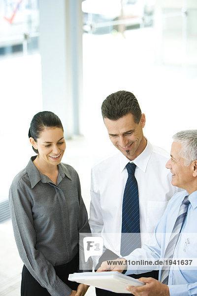 Reife Geschäftsleute  die eine Akte führen und mit Kollegen diskutieren