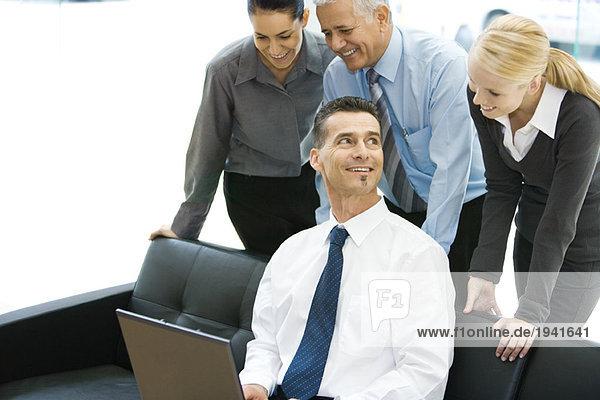 Geschäftsmann mit Laptop-Computer  lächelnd  Mitarbeiter über die Schulter schauend