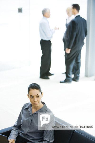 Junge Geschäftsfrau auf dem Sofa sitzend  wegschauend  Mitarbeiter im Hintergrund
