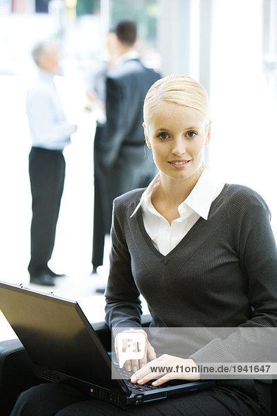 Junge Frau sitzend  mit Laptop-Computer  lächelnd vor der Kamera