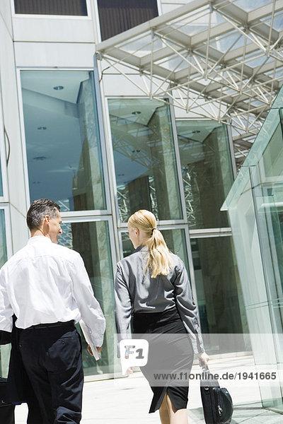 Zwei Geschäftspartner gehen gemeinsam auf das Gebäude zu  Rückansicht