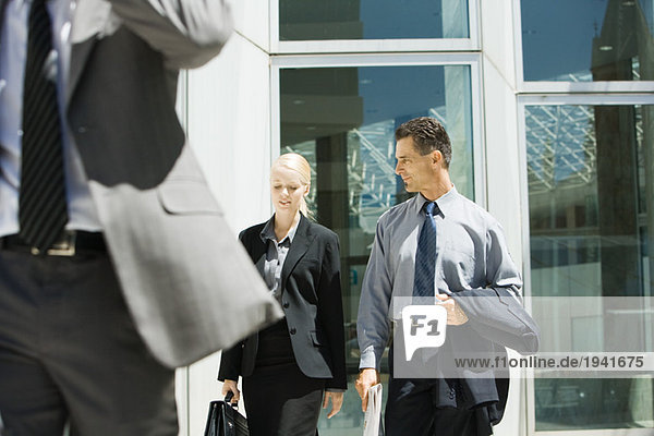 Two business associates walking together  chatting  three quarter length