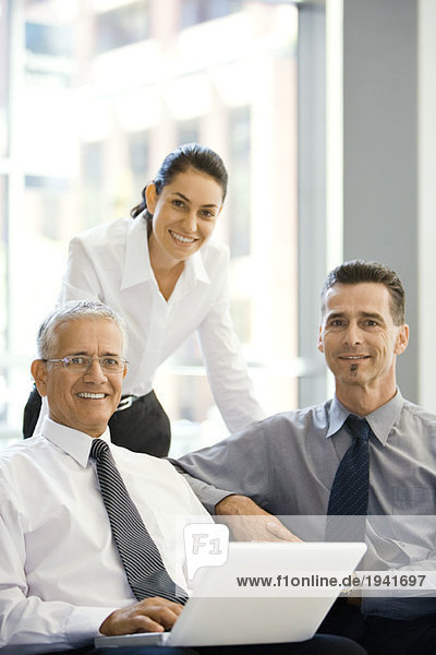 Three business associates smiling at camera  group portrait  one using laptop computer