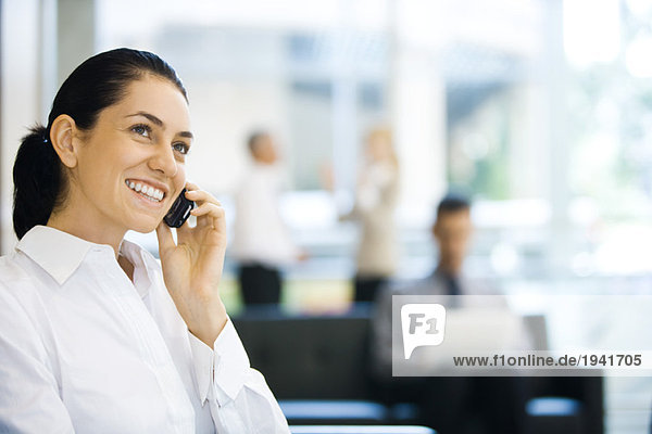 Young businesswoman sitting in lobby  using cell phone  smiling  looking up