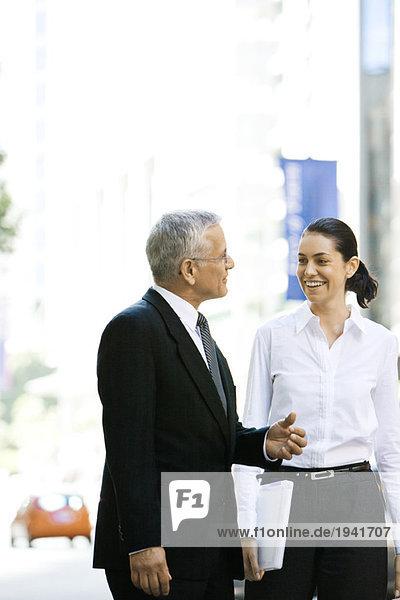 Zwei Geschäftspartner  die zusammen im Freien spazieren gehen  sich anlächeln  sich unterhalten.