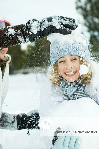 Teenage girl being hit with snowballs  smiling at camera